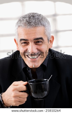 Happy mature businessman drinking tea, smiling.