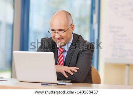 Happy mature businessman looking at laptop at office desk