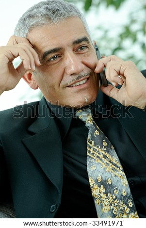 Happy mature businessman talking on mobile phone, smiling, indoor.