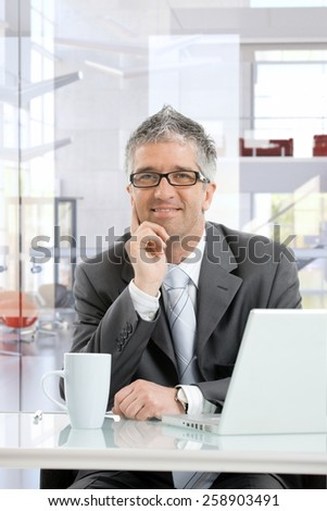 Happy mature businessman thinking at business office desk with laptop computer and coffee mug. Smiling, sitting, hand under chin, looking in the distance, wearing glasses. - stock photo