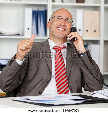 Happy mature businessman using landline phone while gesturing thumbs up at office desk - stock photo