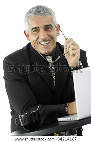 Happy mature businessman using laptop computer at desk, looking at camera, smiling. Isolated on white.