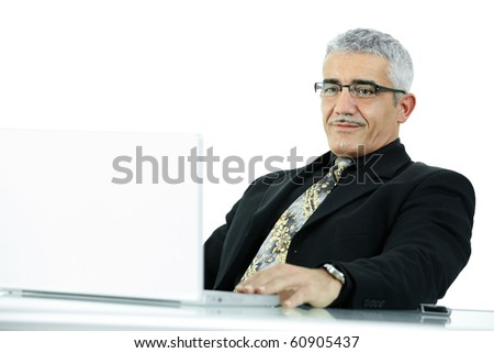 Happy mature businessman working on laptop computer at desk az office, smiling. - stock photo