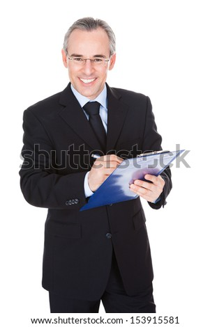 Happy Mature Businessman Writing On Clipboard Over White Background - stock photo