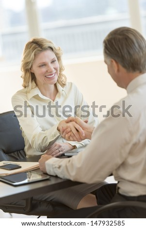 Happy mature businesswoman shaking hands with male colleague at office desk - stock photo