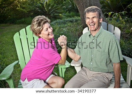 Happy mature couple arm wrestling outdoors. The woman is winning, the man is laughing. - stock photo