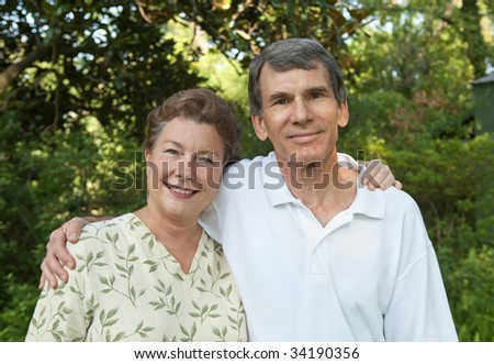 Happy mature couple, arms around each other outdoors. - stock photo
