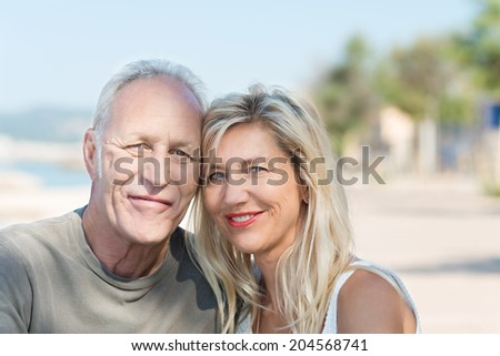 Happy mature couple at the beach smiling - stock photo