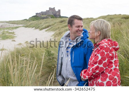 Happy Mature couple at the beach. They are wearing warm casual clothing and a castle can be seen in the distance in the background.  - stock photo