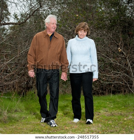 Happy mature couple casually walking outdoors in a park setting.