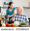 happy mature  couple cooking vegetarian lunch together in domestic kitchen - stock photo