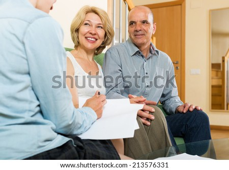 Happy mature couple discussing details of private insurance with agent at home - stock photo