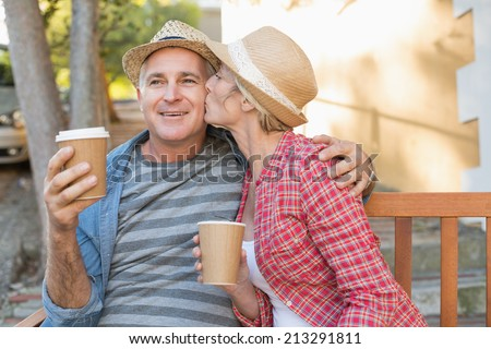 Happy mature couple drinking coffee on a bench in the city on a sunny day - stock photo