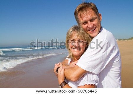 Happy mature couple embracing on a sunny day at the beach - stock photo