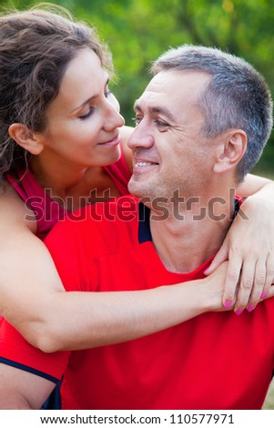Happy mature couple embracing on green park - stock photo