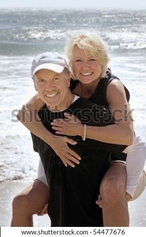 Happy mature couple enjoying a day at the beach - stock photo