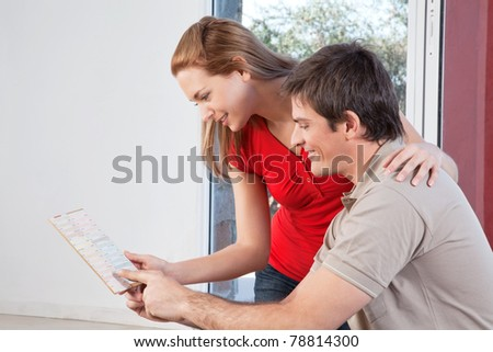 Happy mature couple going through the color swatch for their new house - stock photo