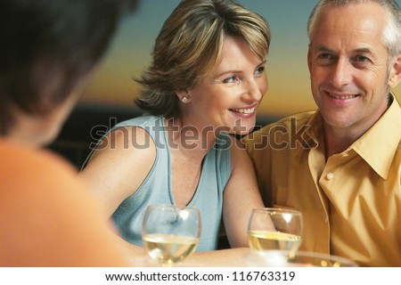 Happy mature couple having a good time on dinner with their friends