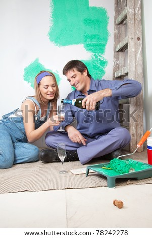 Happy mature couple having champagne at their new apartment - stock photo