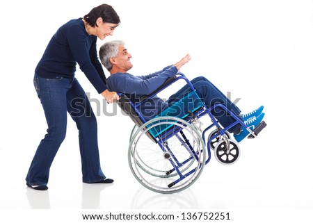 happy mature couple having fun with wheelchair isolated on white background