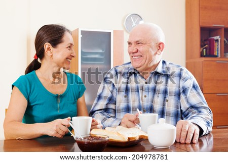 Happy mature couple having tea at home