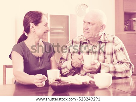 Happy mature couple having tea with jam at home. Focus on man