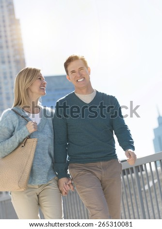 Happy mature couple holding hands while walking together in city - stock photo
