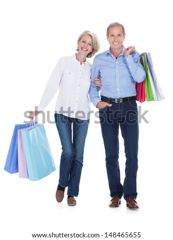 Happy Mature Couple Holding Multi Colored Shopping Bags Over White Background - stock photo