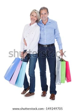 Happy Mature Couple Holding Multi Colored Shopping Bags Over White Background