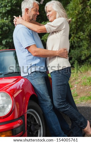 Happy mature couple hugging against their red cabriolet on a sunny day