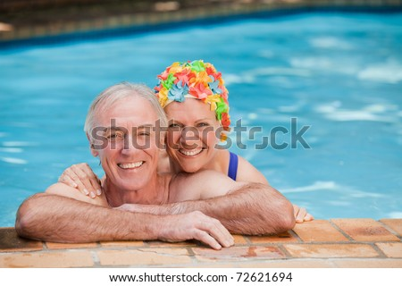 Happy mature couple in the swimming pool - stock photo