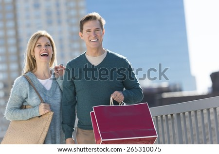 Happy mature couple in warm clothing carrying shopping bag in city - stock photo
