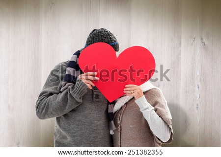 Happy mature couple in winter clothes holding red heart against wooden planks - stock photo