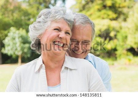 Happy mature couple laughing in the park on sunny day - stock photo