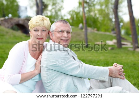 Happy mature couple looking at camera while having rest outside