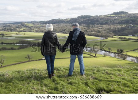 Happy mature couple outdoors over looking a view