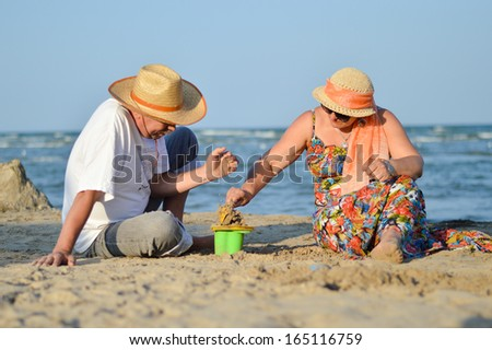Happy mature couple playing at seashore on sandy beach summer outdoors background - stock photo