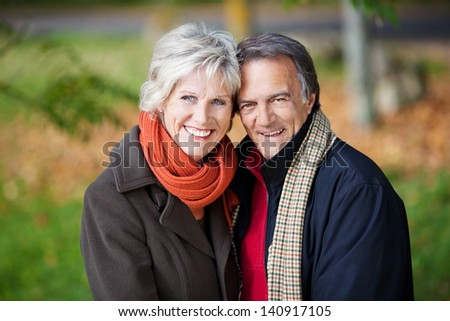 Happy mature couple posing over the outdoors background - stock photo