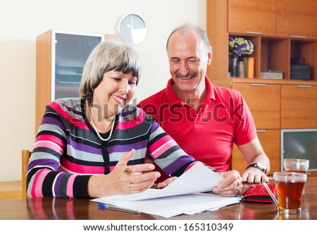 Happy mature couple reading financial documents in home interior - stock photo