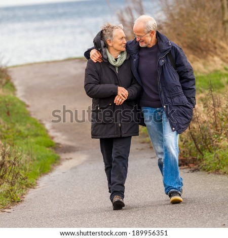 happy mature couple relaxing baltic sea dunes in autumn - stock photo