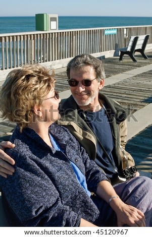 Happy mature couple seated on a park bench on the boardwalk at the ocean.