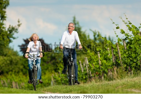Happy mature couple - senior people, man and woman, already retired - cycling in summer in nature - stock photo