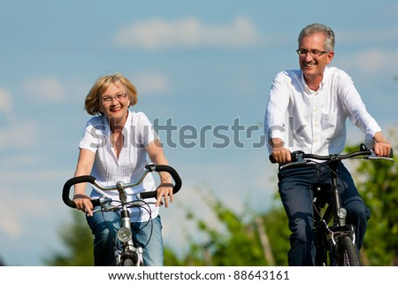 Happy mature couple - senior people (man and woman) already retired - cycling in summer in nature - stock photo