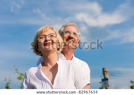 Happy mature couple - senior people (man and woman) already retired - looking to the blue sky in summer - stock photo
