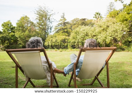 Happy mature couple sitting in park and holding hands - stock photo