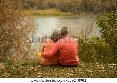 Happy mature couple sitting near lake,back view - stock photo