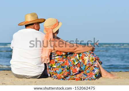 Happy mature couple sitting on sand at seashore having fun outdoors on sandy beach back to back on holiday and looking at sea  - stock photo