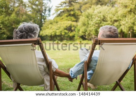 Happy mature couple sitting on sun loungers and holding hands - stock photo