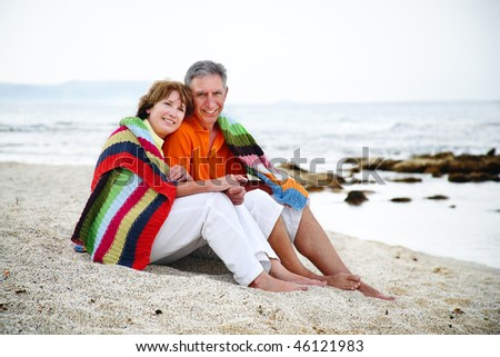 Happy mature couple sitting on the beach. - stock photo