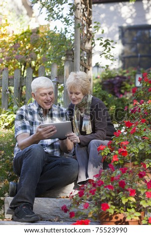 Happy mature couple sitting outside using a digital tablet